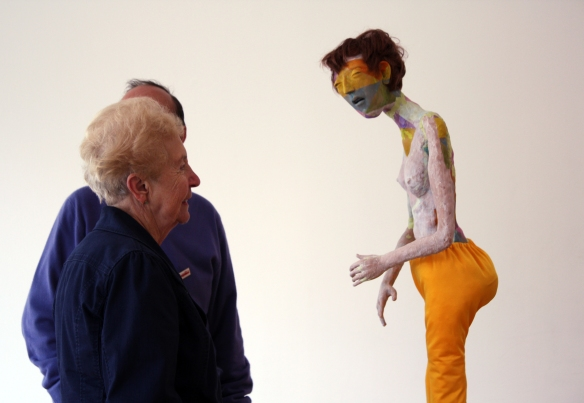 Eileen looking at a figure, bare on top wearing bright yellow trousers